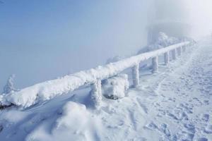 Winterlandschaft und Holzkreuz mit mattem Schnee im Nebel foto