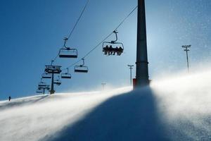 Hintergrundbeleuchtete Szenen mit Skiliftstühlen foto