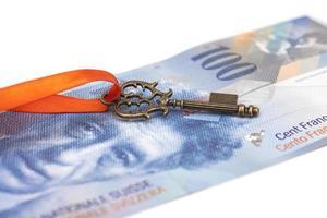 Schlüssel zum Erfolg mit roter Schleife auf Schweizer Franken foto