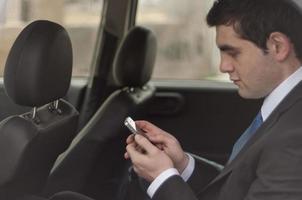 vielbeschäftigter Geschäftsmann in einem Auto foto