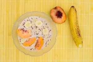 Frühstücksjoghurt mit Pfirsich-, Bananen- und Leinsamen foto