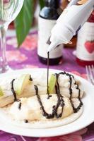 Quarkdessert mit Bananen-, Birnen- und Schokoladensauce foto