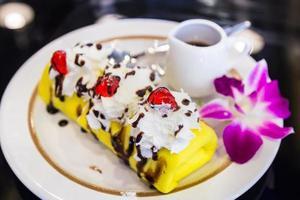 Nahaufnahme Crêpe Kuchen Banane mit Schokolade und rotem Gelee foto