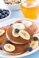 Pfannkuchen mit Banane, Honig und Blaubeere, vertikal foto
