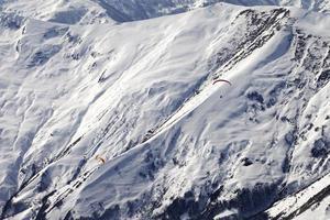 Gleitschirme von schneebedeckten Bergen