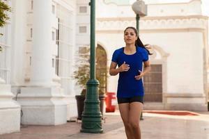 süßes Mädchen, das in der Stadt joggt foto