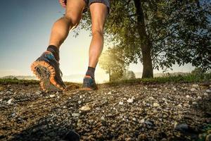 Schließen Sie sich den Schuhen eines Mannes an, der auf dem Land läuft foto