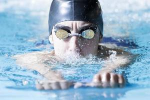 junger männlicher Schwimmer, der mit einem Schwimmbrett schwimmt