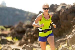 Frau läuft in den Bergen, Sommertag foto
