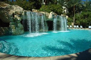 Wunderschöner Wasserfall im klaren Pool des Resorts foto