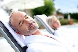 glücklicher Mann mittleren Alters, der an sonnigem Tag entspannt