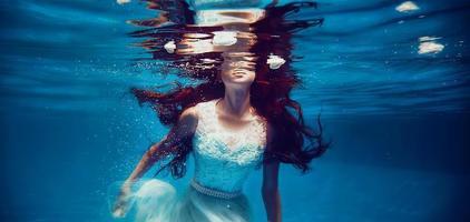 Mädchen schwimmt unter Wasser foto