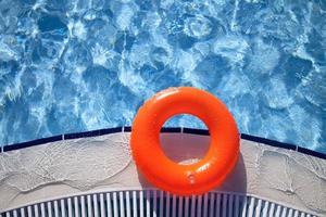 schwimmender orange Ring am Rand des Schwimmbades foto
