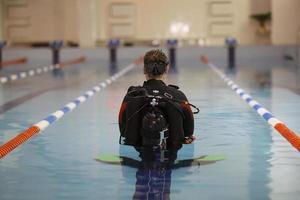 Mann unterrichtet Tauchen im Pool, Schwimmtrainer foto