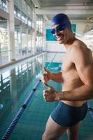Schwimmer gestikuliert Daumen hoch am Pool im Freizeitzentrum