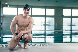 junger muskulöser Schwimmer mit Schutzbrille und Badekappe