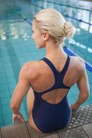 Rückansicht einer gesunden Schwimmerin, die am Pool sitzt foto
