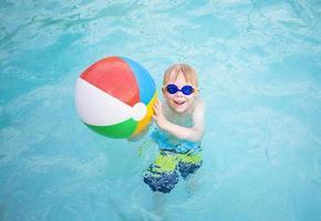 süßer kleiner Junge, der mit Strandball im Schwimmbad spielt foto