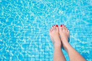 Frauenbeine mit rotem Nagel im Schwimmbad foto
