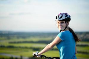 gesunde fröhliche junge Frau, die Fahrrad draußen Land lanscape reitet foto