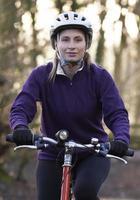 Frau, die Mountainbike durch Wälder reitet foto