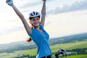 gesunde fröhliche junge Frau, die Fahrrad reizenden schönen Landschaftshintergrund fährt foto