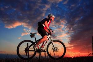 Mann mit Fahrrad am Sonnenuntergang im Freien foto