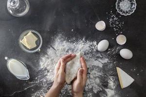 Frauenhände kneten Teig auf dem Tisch mit Mehl foto