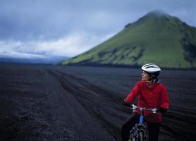 Frau Mountainbiken in der ländlichen Landschaft foto