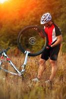junger Mann, der Mountainbike im Wald repariert foto