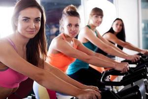Gruppe von vier Frauen im Fitnessstudio Radfahren foto