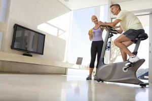 Frau lächelt Mann, der stationäres Fahrrad im Wohnzimmer reitet