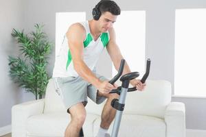 sportlich gutaussehender Mann, der auf Heimtrainer trainiert, der Musik hört foto