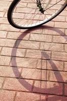 Schatten vom Fahrrad auf roter Backsteinstraße foto