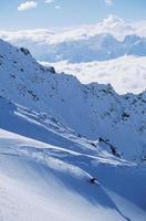Skifahrer, der den Hang hinunter fährt foto