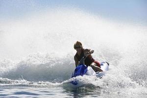 junger Mann, der Jetski in Geschwindigkeit auf See reitet