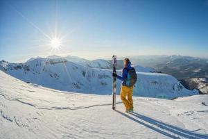 Skifahrer, der Sonnenuntergangansicht von der Spitze des schneebedeckten Berges betrachtet foto