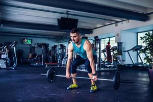 Sportlehrer im Fitnessstudio, der Kreuzhebenübungen macht