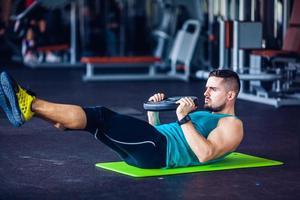 Sportlehrer im Fitnessstudio, der Bauchmuskelübungen macht