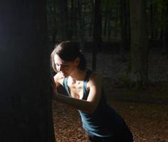 Joggingfrau macht Liegestütze gegen Baumstamm foto
