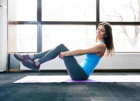 lächelnde junge Frau, die Übung auf Yogamatte macht foto
