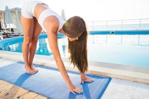 Frau, die draußen auf Yogamatte trainiert foto