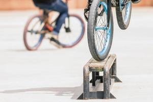 Nahaufnahme von Fahrradrädern, die Trick durch Schiene tun