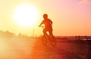 kleiner Junge, der Fahrrad bei Sonnenuntergang reitet foto