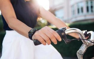 Frau, die Fahrrad mit einer Smartwatch reitet foto