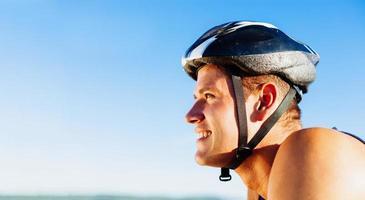junger Mann, der mit Helm auf Kopf radelt foto