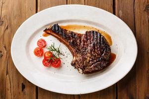 Gegrilltes Ribeye-Steak auf Knochen und Tomaten foto