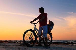 Silhouette von Vater und Baby, die bei Sonnenuntergang radeln