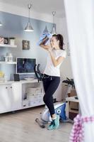 Frau trinkt während des Trainings auf einem Heimtrainer foto