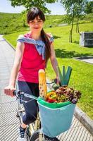 junge sportliche Frau mit Lebensmitteln in einem Korbfahrrad